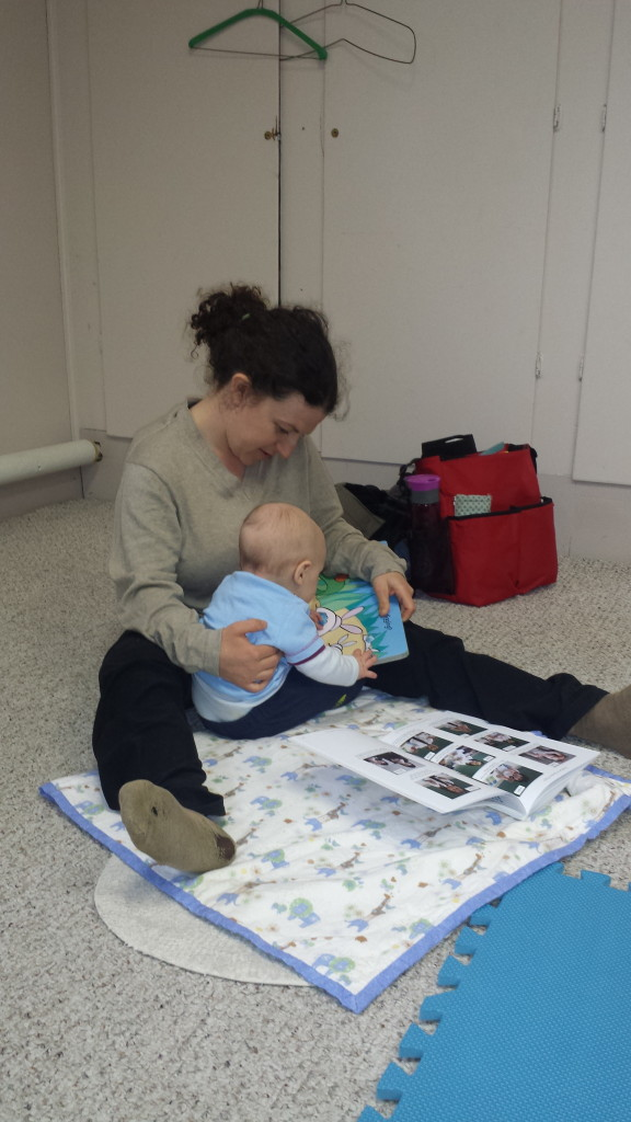 Young baby touches and explores story book.